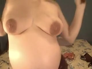 Preggo chick playing with her tits