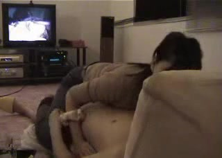Asian couple getting naughty in front of the TV